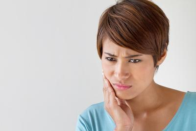 Woman with bad tooth pain from dental emergency near Norfolk MA